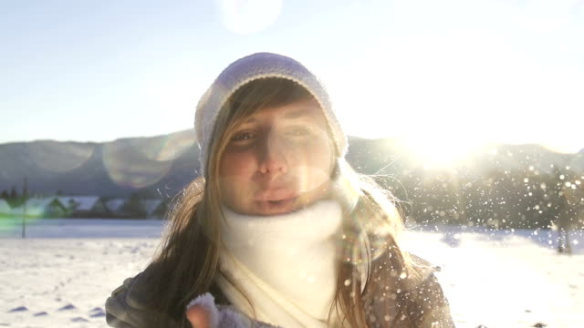 SLOW MOTION: Young woman blowing snowflakes video