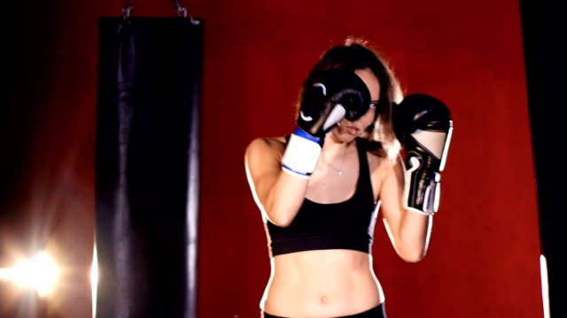 Young woman boxing with punching bags. Slow motion. video