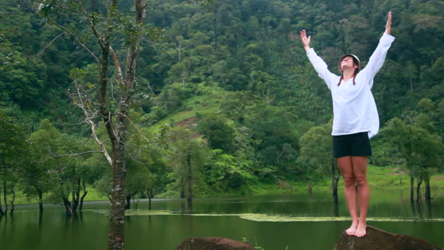Young woman breathing fresh air in rainforest video