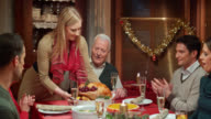 Young woman bringing turkey to family at the table video