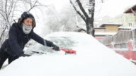 Young woman brushing away the snow from the car. video