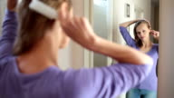 Young woman brushing her hair in front of a mirror video