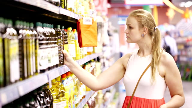 Young woman buying olive oil video