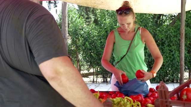 Young Woman Buying Tomatoes at Street Vendor Stall video