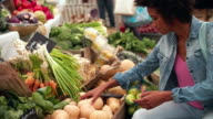 Young woman buying vegetables at a food market stall video