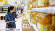 Young woman buys sunflower oil in supermarket video