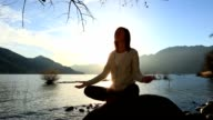 Young woman by the lake exercising yoga at sunset video