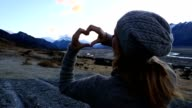 Young woman by the lake makes a heart shape finger frame video