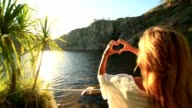 Young woman by the lake makes heart shape finger frame video