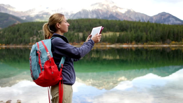Young woman by the lake photographing landscape using digital tablet video
