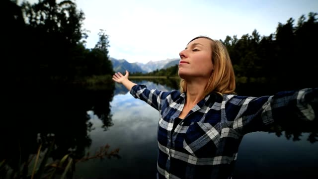 Young woman by the lake stands arms outstretched for freedom and positive emotions video