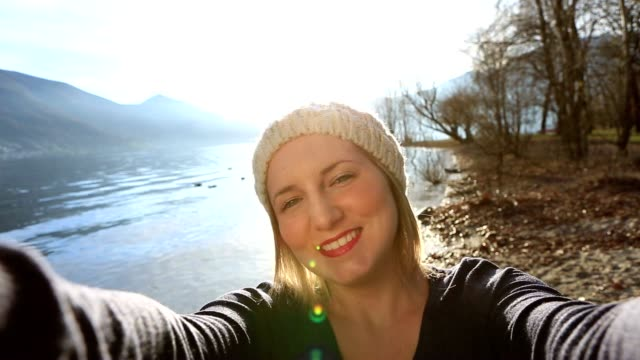 Young woman by the lake takes a selfie portrait video