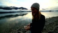 Young woman by the lake uses smart phone video