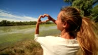 Young woman by the river makes heart shape finger frame video