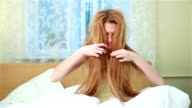 A young woman can not comb his terribly confusing red hair sitting on a bed in a bedroom. video