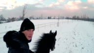 Young woman cantering with big black horse video