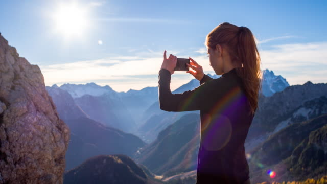 Young woman capturing memories with her smartphone video