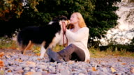 Young woman caresses her dog. Sitting on a beach of pebbles, stroking her Australian shepherd video