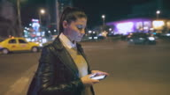 Young woman checking her smart phone while waiting for Uber. video