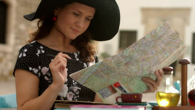 Young woman checking map, satisfied with journey plan, making notes video