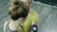 A young woman checks blood pressure In The Gym video