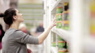 Young woman chooses canned food in the store video