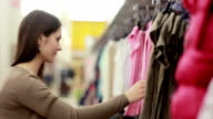 young woman chooses clothes for a child video
