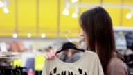young woman chooses clothes in store video