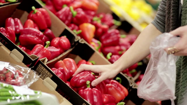 Young woman chooses paprika on store shelves video