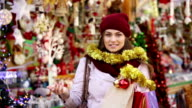 young woman choosing Christmas decoration video