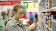 Young woman choosing food in supermarket. video