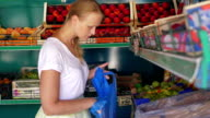 Young woman choosing pears in fruit shop video