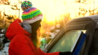 Young woman cleaning car windows from snow in winter season video