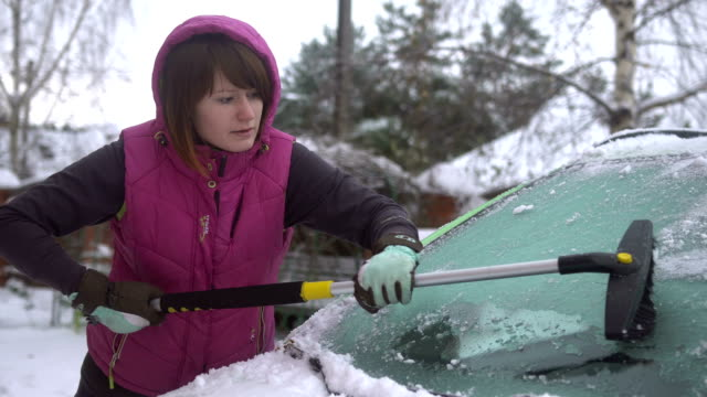 Young woman cleaning Snow and Ice off her Car. Winter snow storm video