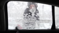 Young woman cleaning the ice from the car with the brush. video