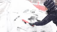 Young woman cleaning the snow from a car. video