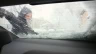 Young woman cleaning the snow from the rear window of the car. video