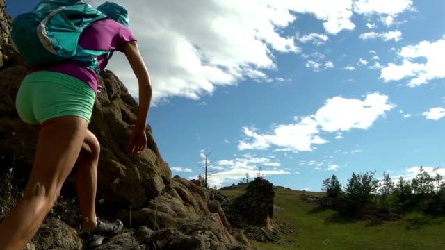 Young woman climbing to the mountain video