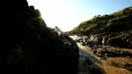 Young woman climbs steep rock, towards sunlight video