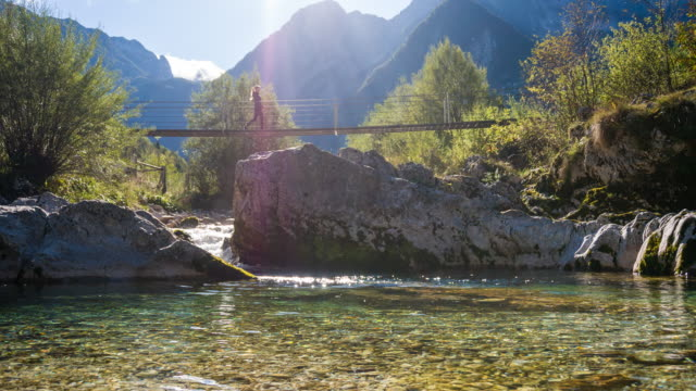 Young woman crossing a suspension bridge over mountain stream video