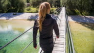 Young woman crossing a wooden suspension bridge over a stream video