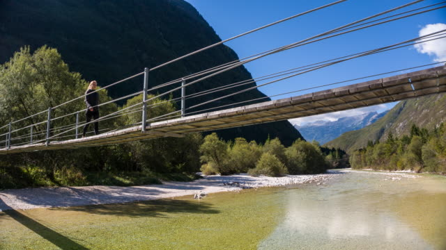 Young woman crossing a wooden suspension bridge over mountain stream video