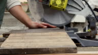 A young woman cuts wood with an electric saw. video