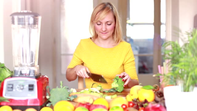 Young woman cutting broccoli video