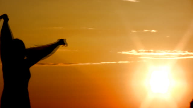 Young woman dancing with scarf in the sunset video