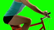 Young woman doing a fitness routine on bike. Green screen video
