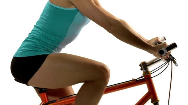 Young woman doing a fitness routine on bike. White screen video