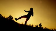 SLOW MOTION: young woman doing funny jump at sunset video