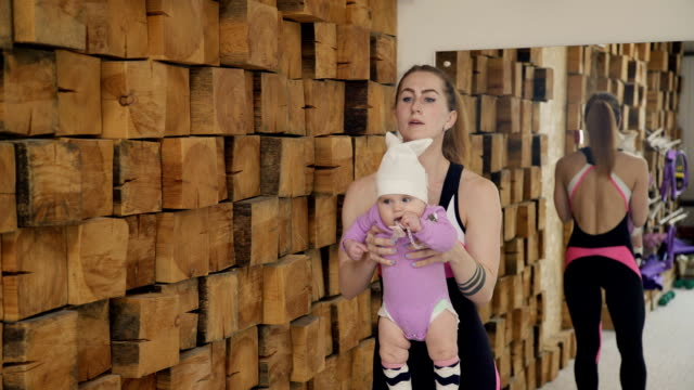 Young woman doing lunges holding little baby in arms indoors video