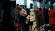 Young woman doing makeup on a model in the boutique of women's clothing. video